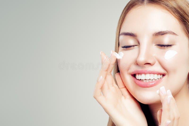 Closeupskönhetstående av att skratta kvinnan med sund hud som applicerar kosmetisk kräm på hennes framsida royaltyfri bild
