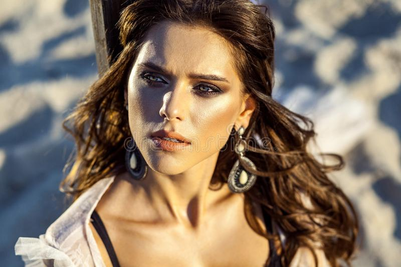 Closeupskönhetstående av den attraktiva brunettkvinnan som poserar på den sandiga stranden på solnedgången med makeup, örhängen o arkivbilder