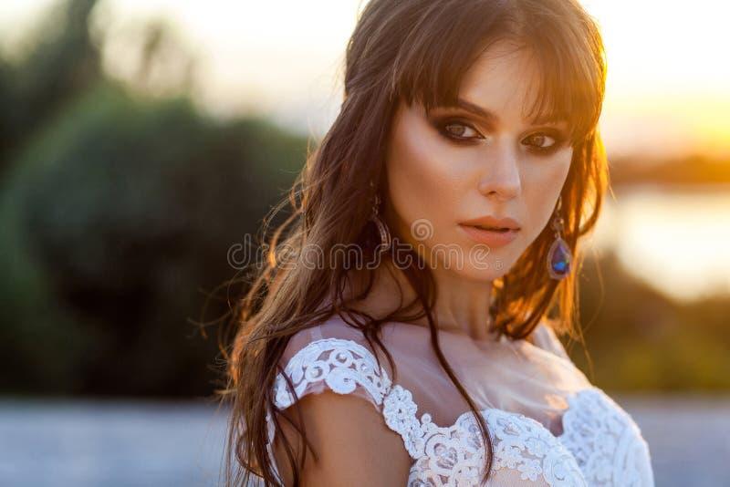 Closeupskönhetstående av den gulliga lugna brunettkvinnan med den bärande vita bröllopsklänningen för makeup och för frisyr på su royaltyfri foto