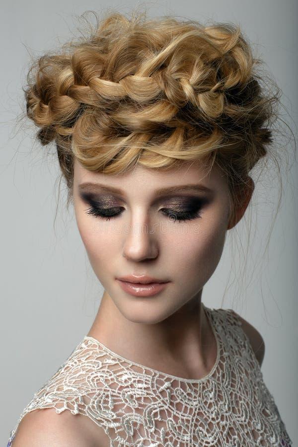 Closeupskönhetståenden av en blond flicka med makeup för mörkt öga och flätade trådar som bands runt om hennes huvud med henne ög arkivfoto