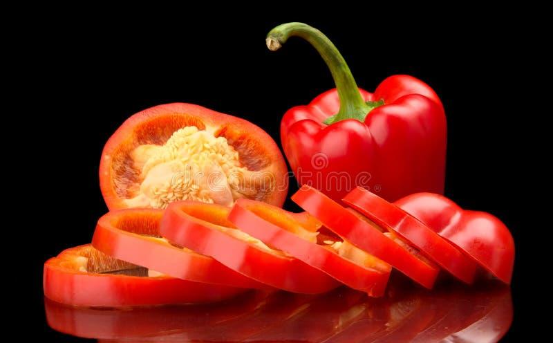 Closeupskivor av röda spanska peppar som isoleras på svart royaltyfri foto