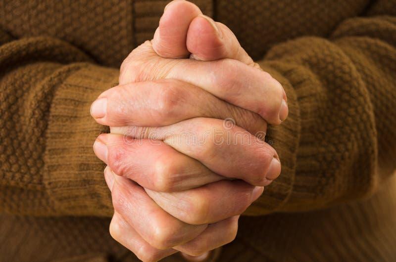 Closeupskott av farmors att be för händer arkivbild