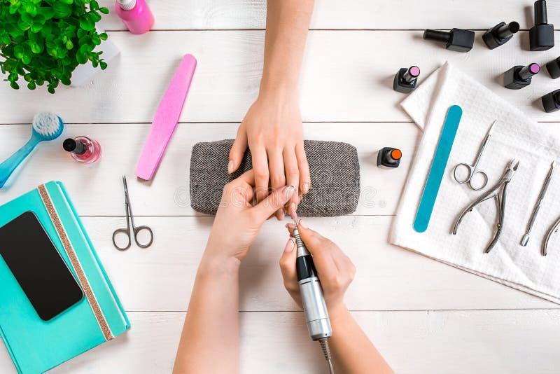 Closeupskottet av en kvinna i en spikasalong som mottar en manikyr av en kosmetolog med, spikar mappen Att få för kvinna spikar m royaltyfri foto