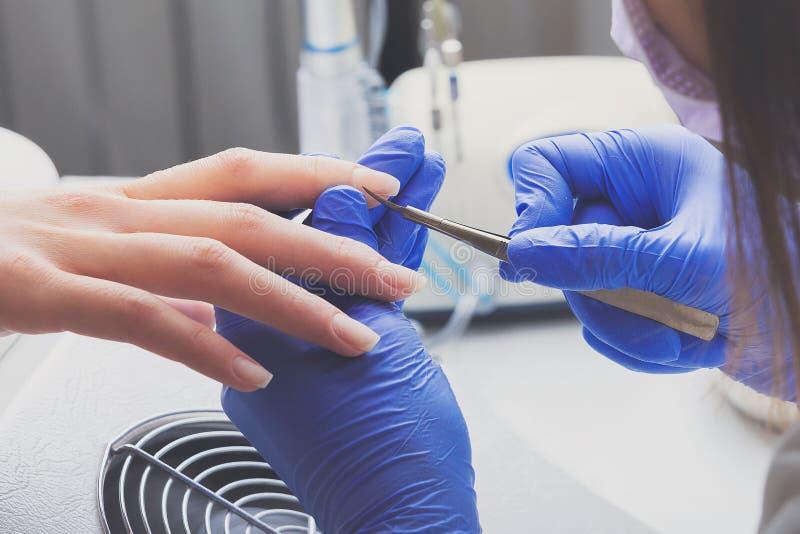 Closeupskottet av manikyristen i blåa rubber handskar och medicinsk maskering tar bort nagelbandet på kvinnlig spikar genom att a arkivbilder