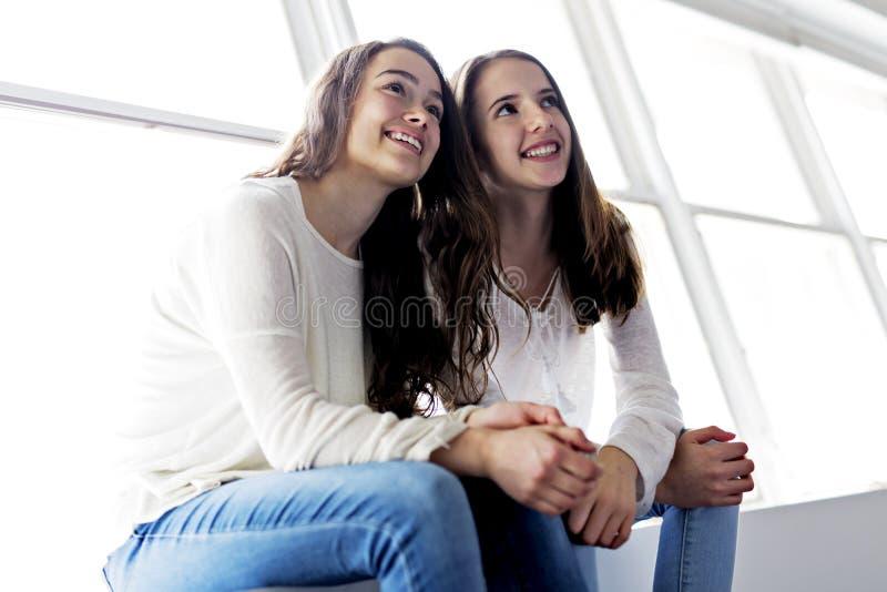 Closeupstående av att krama 2 härliga unga kvinnor som har gyckel royaltyfria foton