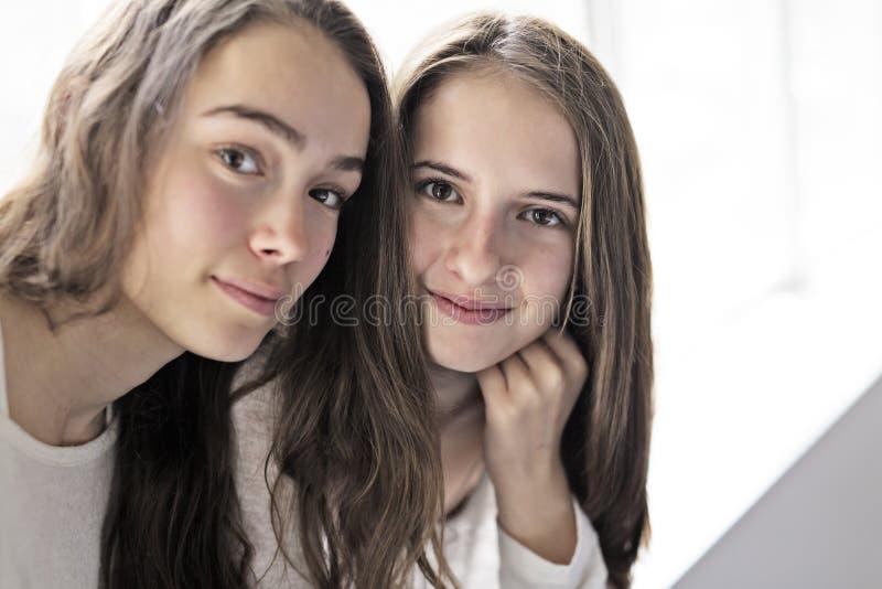 Closeupstående av att krama 2 härliga unga kvinnor som har gyckel royaltyfri bild
