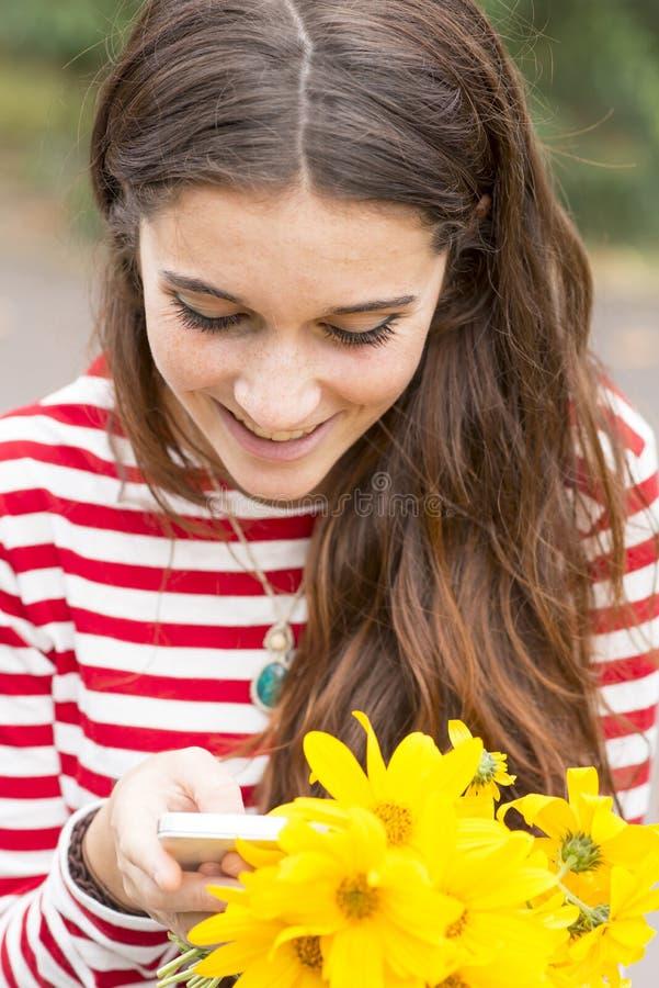 Closeupstående av att le den lyckliga flickan med blommor som ser röra royaltyfri fotografi
