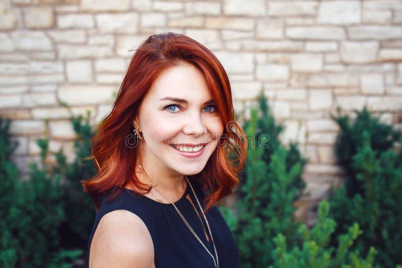 Closeupstående av att le den mitt åldrades vita caucasian kvinnan med vinkat lockigt rött hår i den svarta klänningen som in came fotografering för bildbyråer