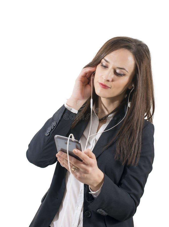 Closeupstående av den älskvärda unga kvinnan som tycker om musik genom att använda hörlurar royaltyfri fotografi