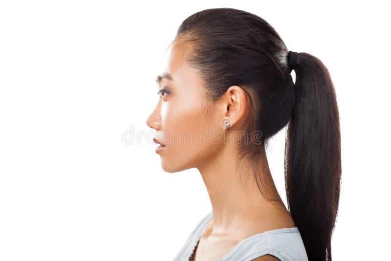 Closeupstående av den asiatiska unga kvinnan i profil med hästsvansen arkivbild