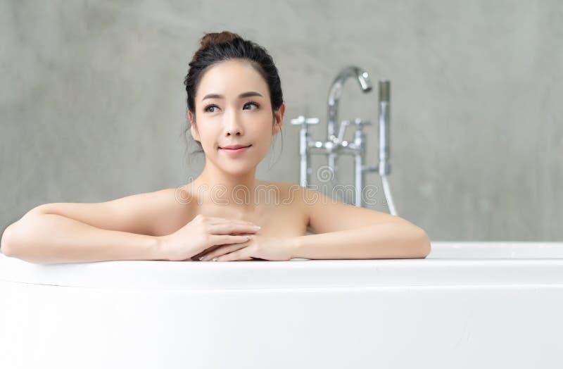 Closeupst?ende av den attraktiva asiatiska damen som bort kopplar av och ser, medan sitta i bathtuben Spa behandlingar f?r sk?nhe fotografering för bildbyråer