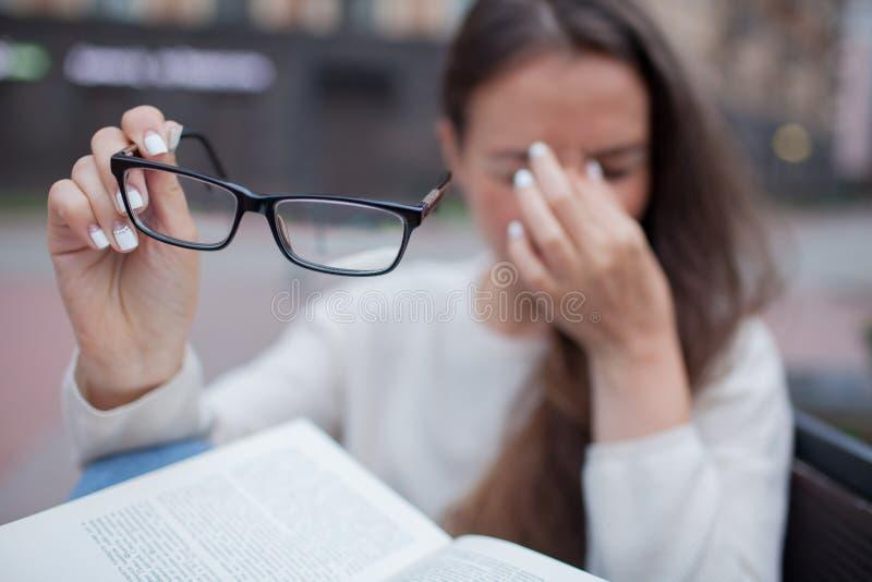 Closeupstående av den attraktiva kvinnlign med glasögon i hand Den fattiga unga flickan har frågor med vision Hon gnider hennes n royaltyfri bild