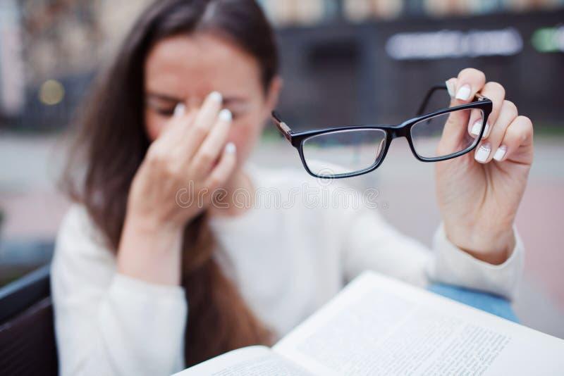 Closeupstående av den attraktiva kvinnlign med glasögon i hand Den fattiga unga flickan har frågor med vision Hon gnider hennes n royaltyfria bilder
