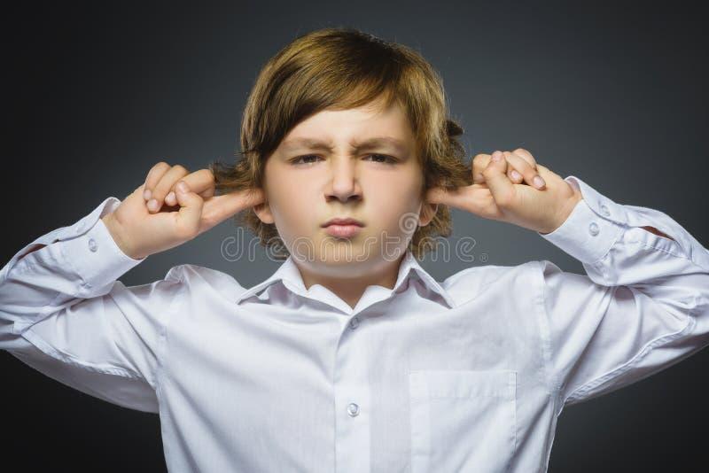 Closeupstående av den bekymrade pojken som täcker henne öron och att observera hör ingenting Mänskliga sinnesrörelser, ansiktsutt fotografering för bildbyråer