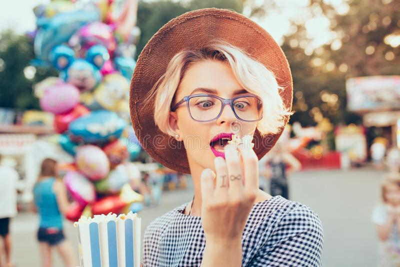 Closeupstående av den blonda flickan med kort frisyr som är utomhus- på baloonsbakgrund Hon bär den rutiga klänningen, hatt arkivbilder