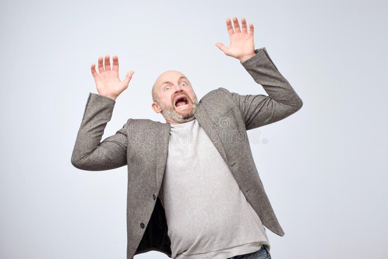 Closeupstående av den chockade bedövade förvånade mogna mannen i tillfällig dräkt, händer i luft som skriker och att skrika eller arkivfoto