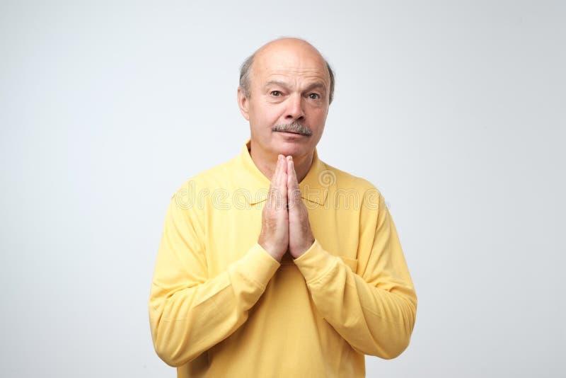 Closeupstående av den desperata mogna mannen i gul knäppte fast händer för skjorta visning och att fråga för hjälp eller ursäkt arkivbild