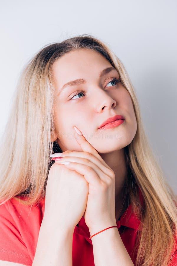 Closeupstående av den eftertänksamma ledsna unga blonda kvinnan på vit royaltyfria foton