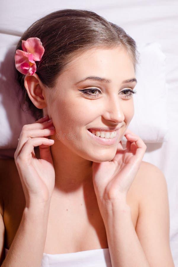 Closeupstående av den gladlynta unga härliga kvinnan som ligger i brunnsortsalongen royaltyfria bilder