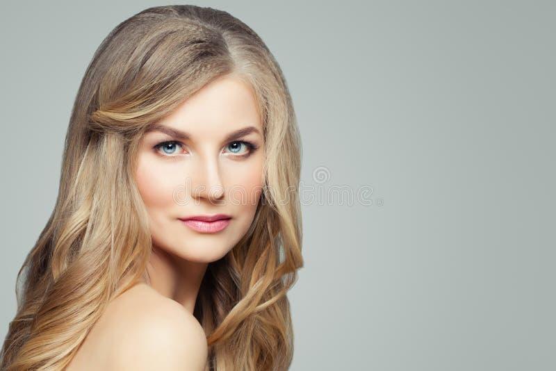 Closeupstående av den härliga blonda kvinnaframsidan Spa modell med lång sund lockigt hår och hud royaltyfri foto