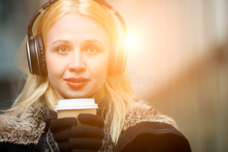 Closeupstående av den härliga blonda kvinnan med hörlurar och kaffe arkivbild