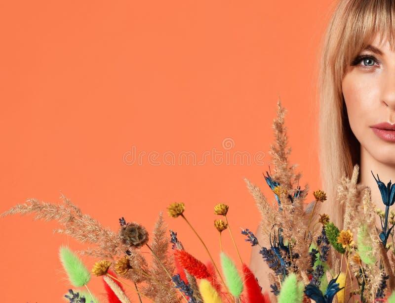 Closeupstående av den härliga kvinnan för blåa ögon med buketten av naturliga lösa blommor på apelsinen royaltyfri foto