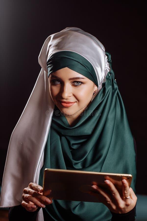 Closeupstående av den härliga kvinnan i hijab med minnestavlan i händer arkivfoton