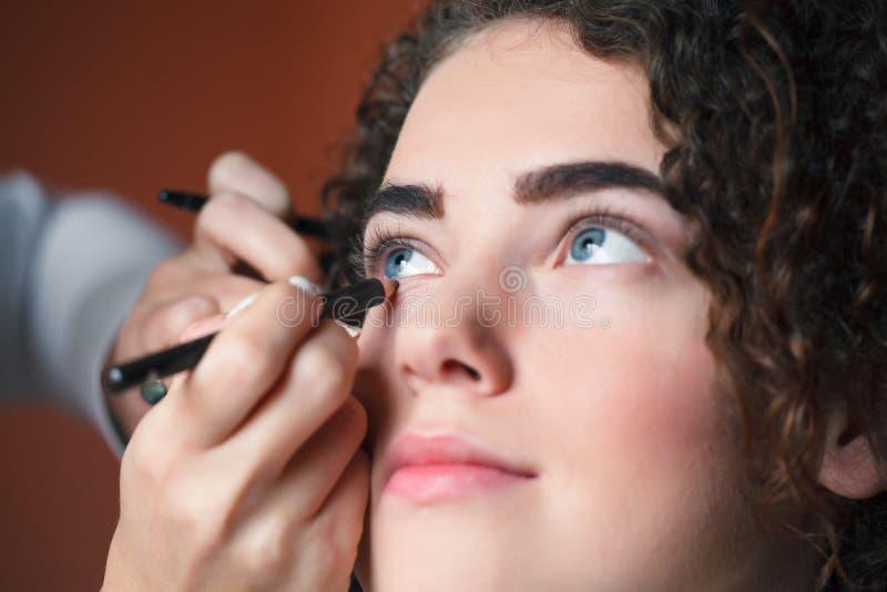 Closeupstående av den härliga kvinnan som får yrkesmässigt smink med borsten Skönhet och makeupbegrepp arkivfoto
