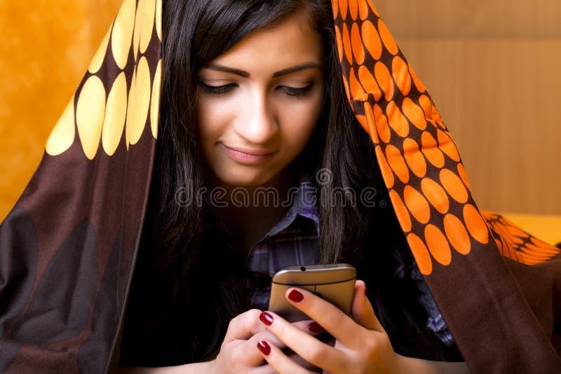 Closeupstående av den härliga tonårs- flickan som använder den dolde mobil telefonen royaltyfria foton