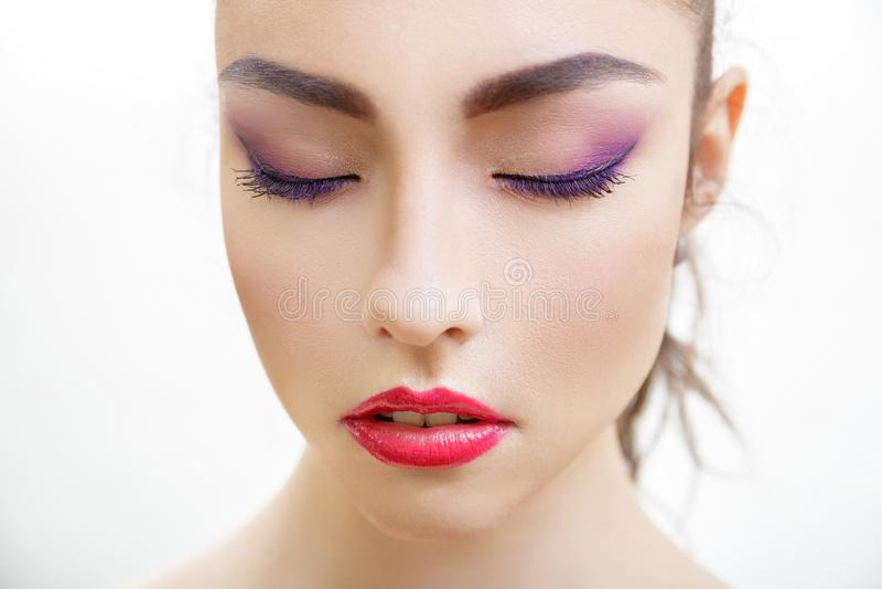 Closeupstående av den härliga unga kvinnan med ljusa purpurfärgade makeup- och fuchsiakanter royaltyfri foto