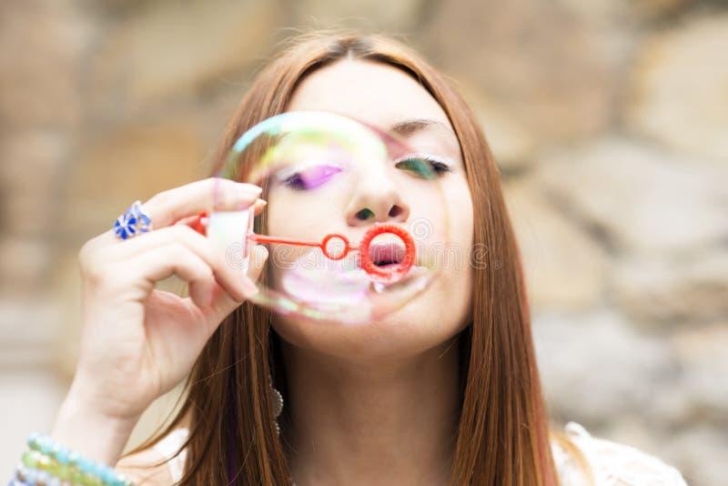 Closeupstående av den härliga unga kvinnan som blåser upp färgrik soa arkivfoto