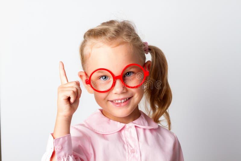 Closeupstående av den härliga unga le flickan som pekar med pekfingret uppåt royaltyfri foto