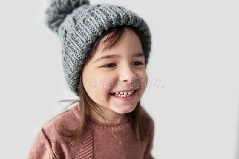 Closeupstående av den lyckliga gulliga lilla flickan i tröjan för hatt den vinter som varma gråa för le och bära, isoleras på en  arkivbild