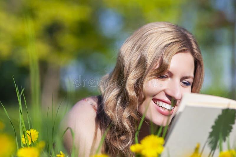 Closeupst?ende av den lyckliga le Caucasian kvinnlign med liggande och l?sande det fria f?r bok p? gr?smatta royaltyfri foto