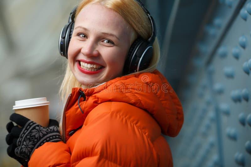 Closeupstående av den lyckliga le kvinnan med hörlurar och kaffe royaltyfri fotografi