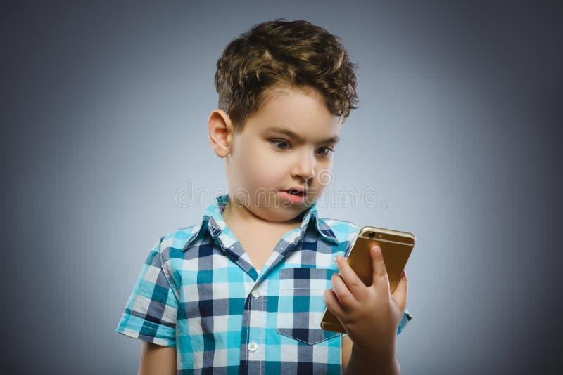 Closeupstående av den lyckliga pojken med mobil gående överraskning på grå bakgrund arkivbilder