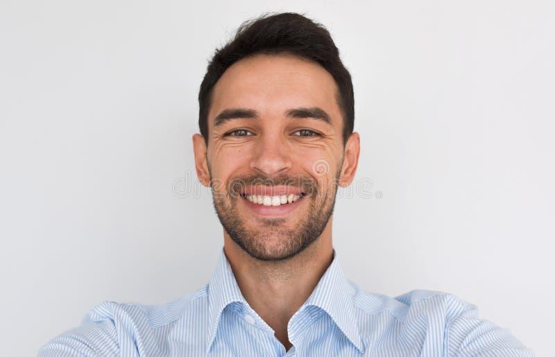 Closeupstående av den lyckliga stiliga unga mannen som ler med det healhty toothy leendet som ser kameran som gör självståenden arkivbilder