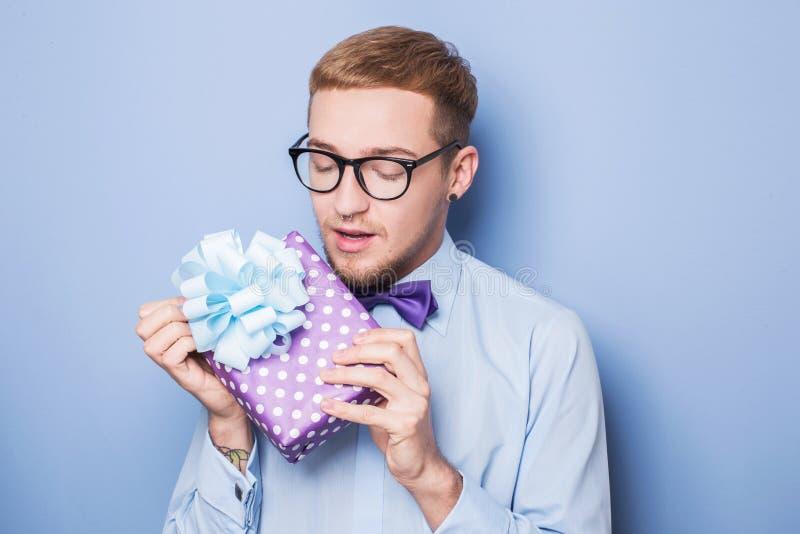 Closeupstående av den lyckliga upphetsade unga mannen med den färgrika gåvaasken Gåva födelsedag, valentin arkivfoto