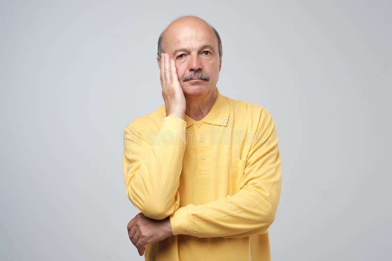 Closeupstående av den mogna deprimerade mannen i gula den egentligen ledsna som skjortan är djup i tanke som ser fråga upp fråga  arkivfoton