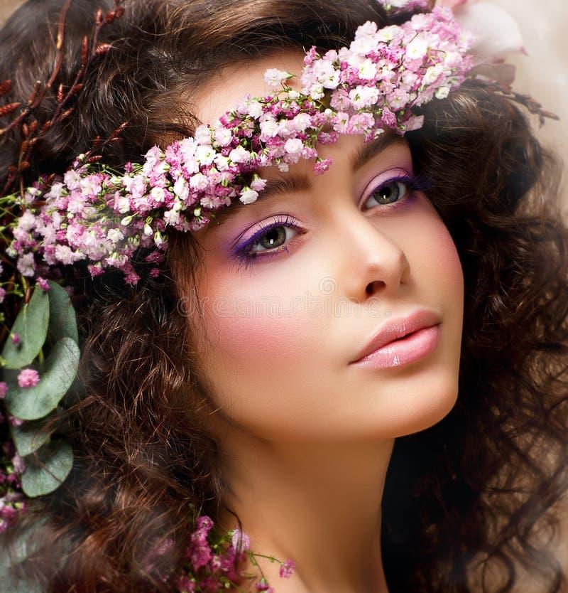 Closeupstående av den nätt kvinnan med kranen av rosa blommor. Naturlig skönhet royaltyfri foto