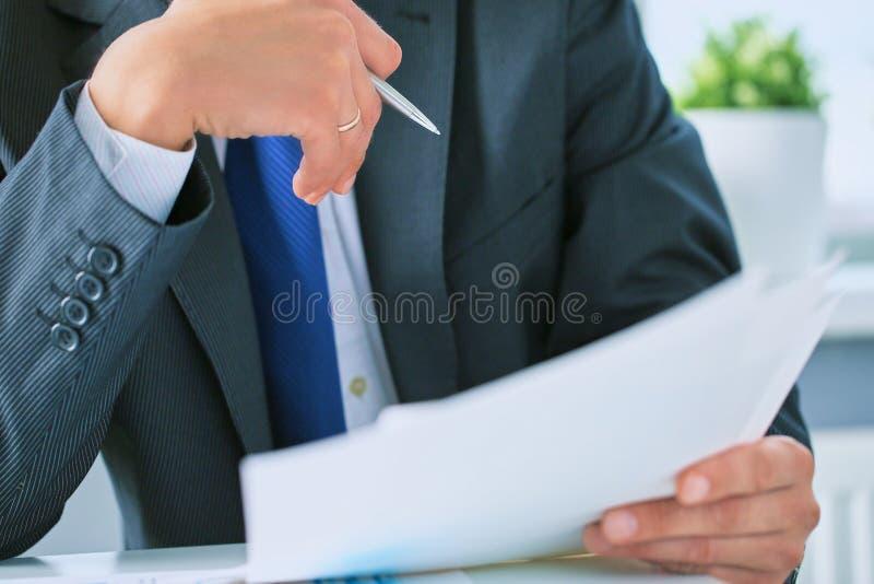 Closeupstående av den oigenkännliga affärsmannen i svart formell dräkt som läser avtalsdokument på skrivbordet i kontoret royaltyfria bilder