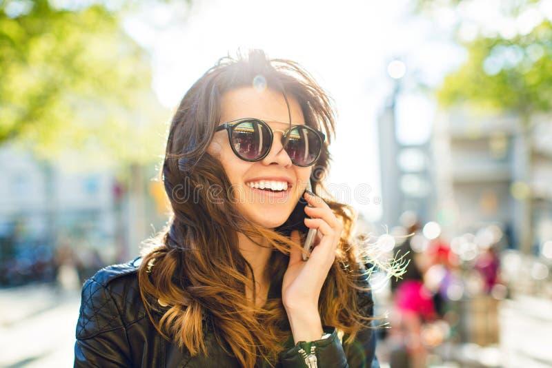Closeupstående av den positiva brunettflickan som talar på telefonen på den blåsiga soliga gatan Hon bär solglasögon, svart omsla arkivbild