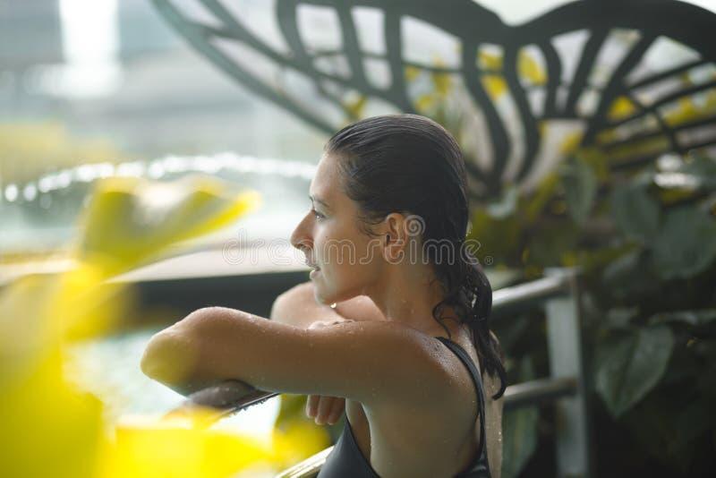Closeupstående av den sexiga slanka kvinnlign i simbassäng mellan gröna buskar royaltyfri foto