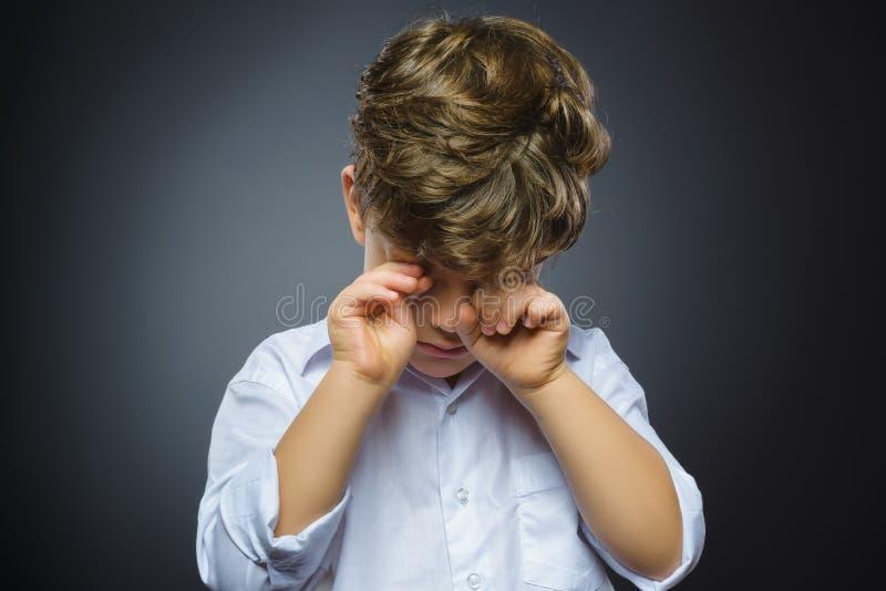Closeupstående av den skriande pojken med förvånat uttryck, medan stå mot grå bakgrund royaltyfri fotografi
