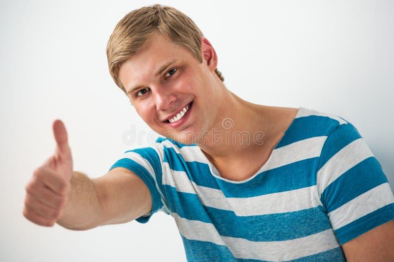 Closeupstående av den stiliga benägenheten för ung man på den vita väggen arkivfoton