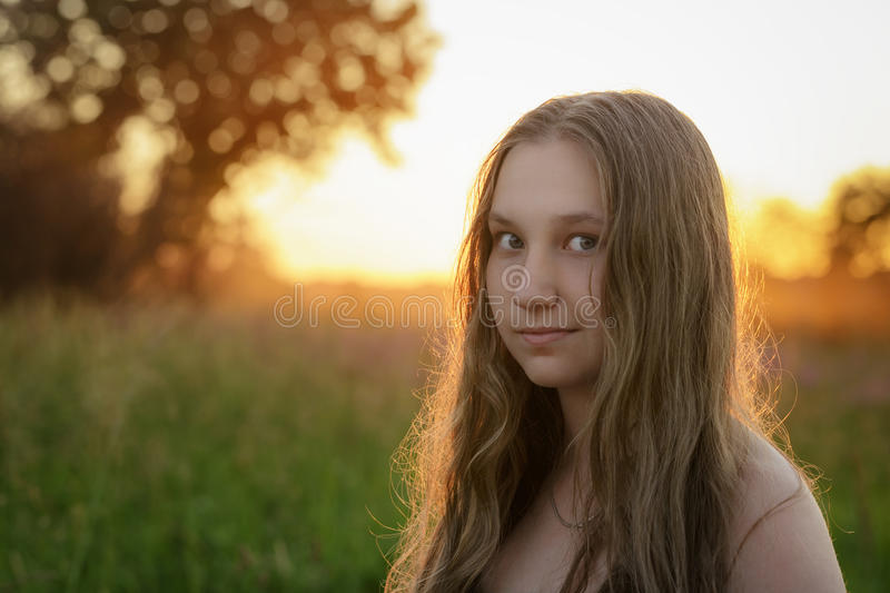 Closeupstående av den tonåriga flickan i solnedgång royaltyfri foto