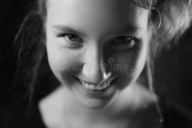 Closeupstående av den tonårs- flickan som ler i mörk studio arkivbilder