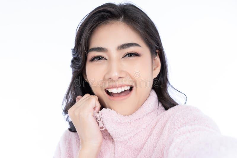 Closeupstående av den unga asiatiska damen som bär stucken smilling för tröja rosa kall och tagande selfie som isoleras över vit  arkivfoton