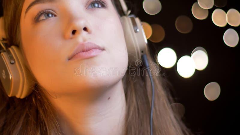 Closeupstående av den unga attraktiva caucasian kvinnlign som lyssnar till musik i hörlurar med bokehljus på arkivbilder