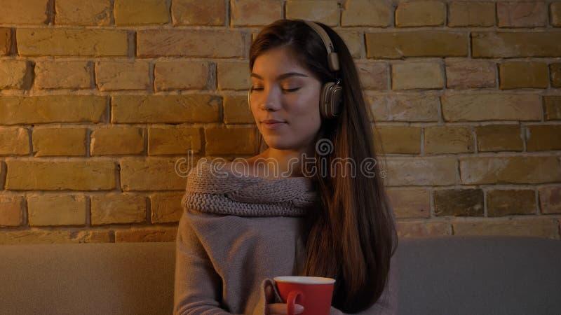 Closeupstående av den unga caucasian kvinnlign som lyssnar till musik i hörlurar, medan sitta på den soffan och tycka om arkivbild